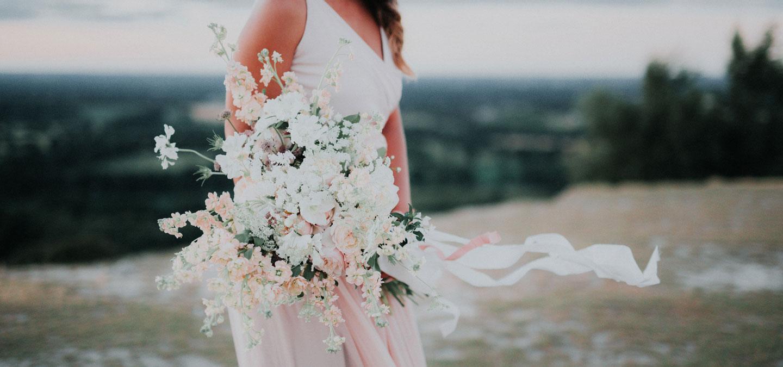 Buste de femme habillée en mariée et tenant un bouquet de fleurs
